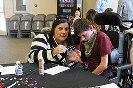 Caregiver Heather Ayers helps her son Zachery to decorate their valentine