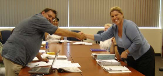 Curt Ostrander of UDW/AFSCME and Lisa Piña of Riverside County Human Resources shake hands on the historic agreement between UDW and Riverside County that would utilize all available state and federal funding  to support homecare providers within the life of the contract