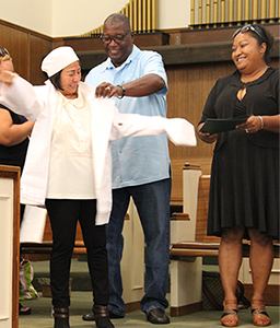 UDW home care provider and Culinary Arts Academy graduate receiving her white chef's coat.